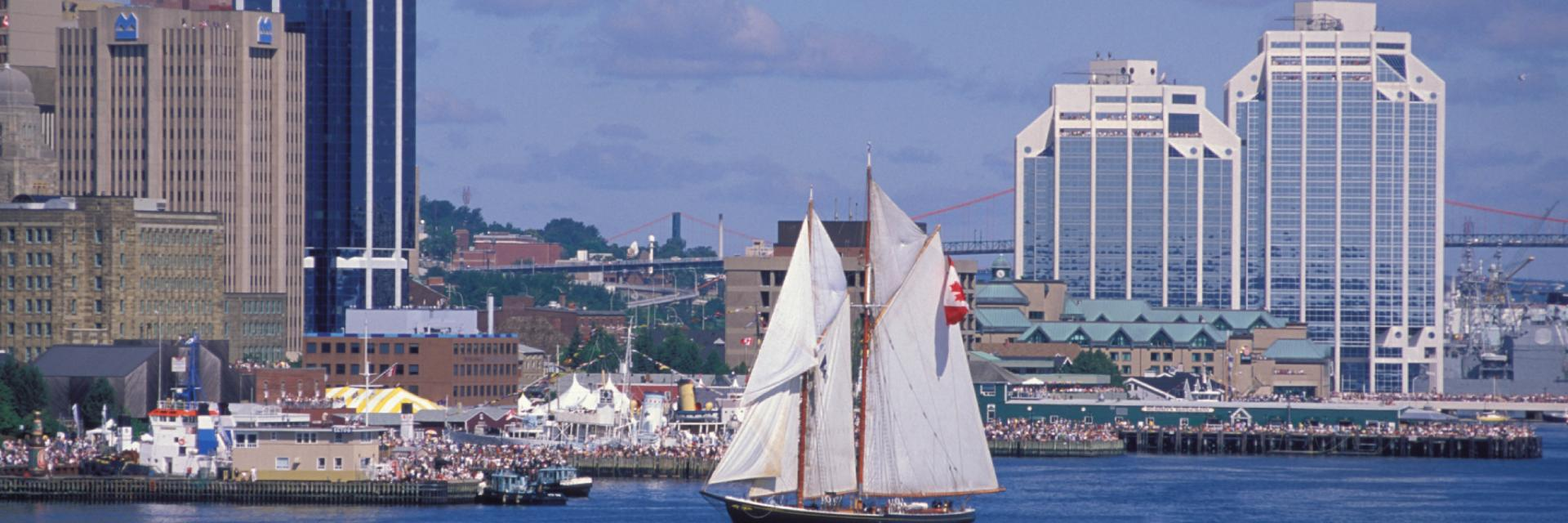 The Bluenose II sails in Halifax harbour with downtown buildings in the background.