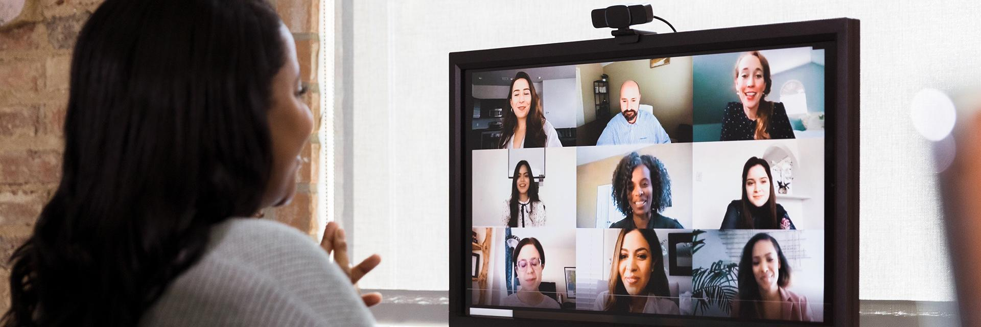 A multi-ethnic team of co-workers meet together via video conferencing.